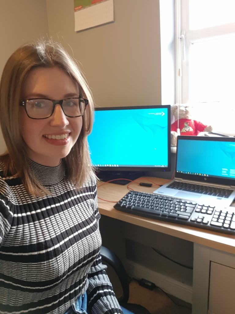 Photograph of Beth Slingsby at work, as shown by two computer monitors behind her. She is smiling and looking into the camera.
