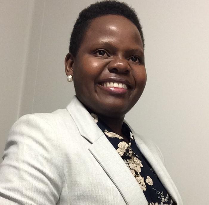 Photograph of Phylis Makurunje smiling while wearing a tan blazer and black shirt.