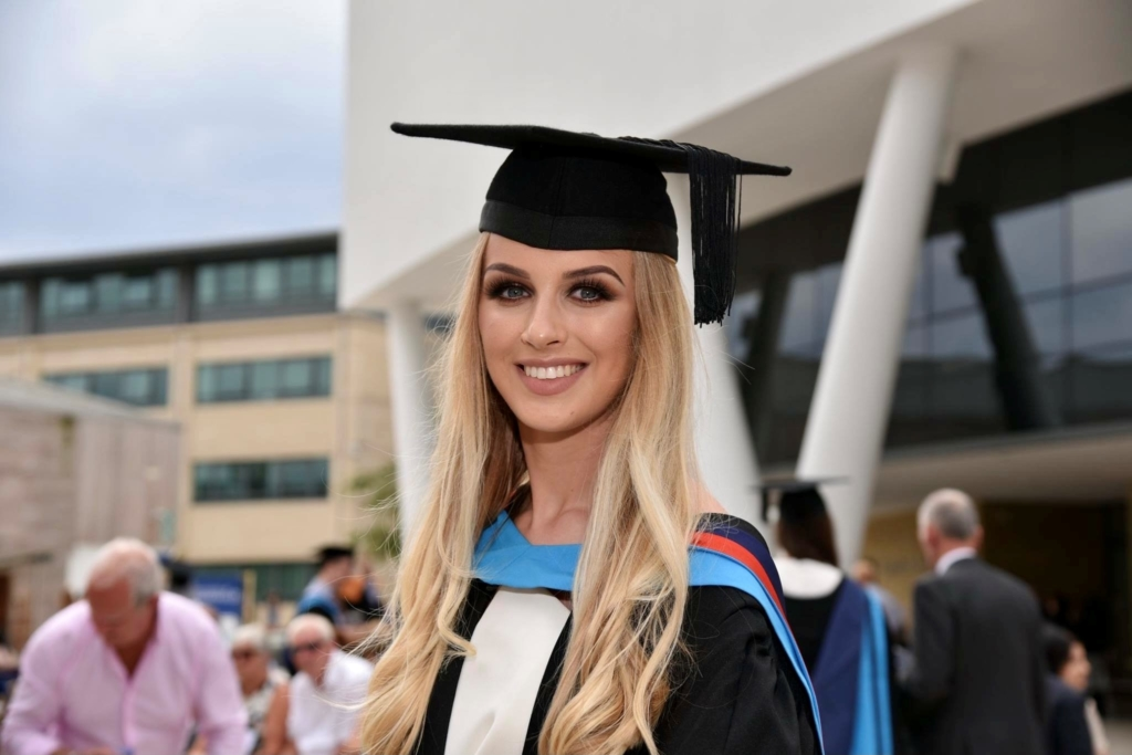 Photograph of Leah Etheridge at her graduation from the University of Huddersfield. She wears a graduation cap and cape.