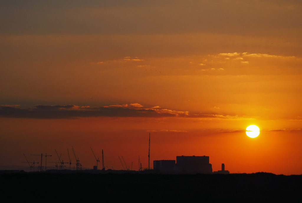 A photograph of the sun setting behind nuclear reactors at Hinkley Point A and B, with Hinkley Point C also under construction.