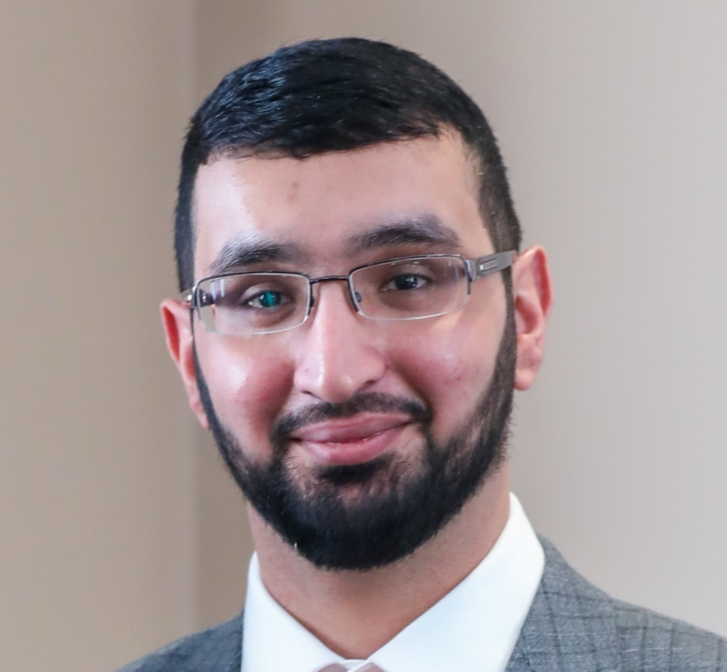 Photograph of AFCP researcher Akeel Ahmed. He is wearing glasses and a suit and looking into the camera, smiling.