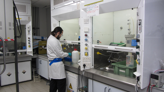 A photo of Ben Day, one of AFCP's early career workers, performing research to optimise the process. He is wearing a white lab coat, standing with his back turned to the camera as he works on an experiment at the bench.